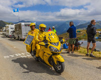 The Yellow LCL Bike - Tour de France 2015. Col de la Croix de Fer, France - 25 July 2015:The yellow LCL timekeeper bike passing before the peloton on the road to Royalty Free Stock Images