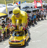Yellow LCL Cyclist Mascot in Alps - Tour de France 2015. Col du Glandon, France - July 23, 2015: LCL characteristic vehicle during the passing of the Publicity Stock Photography