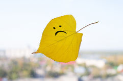 Yellow leaf with a picture of a sad face Stock Image
