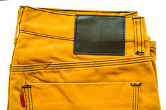 Yellow leather jeans labels Stock Photography