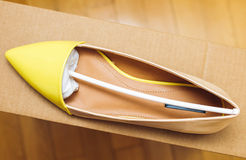 Yellow leather shoe placed on cardboard box Royalty Free Stock Images