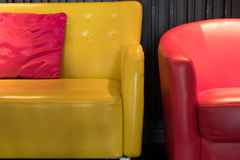 Yellow leather sofa with pink fabric pillow and red armchair. Beside black wall Royalty Free Stock Photos