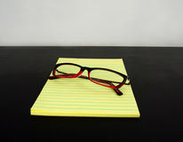 Yellow legal pad on a black table with glasses Stock Photo