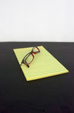 Yellow legal pad on a black table with glasses Royalty Free Stock Photo