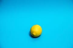 Yellow lemon against a blue background. A yellow lemon against a blue background Royalty Free Stock Photo