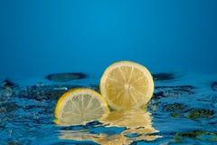 Yellow lemon dropped into water Stock Photo