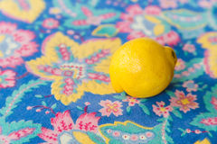 Yellow lemon on floral tablecloth Stock Images