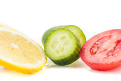 Yellow lemon, green cucumber and red tomato slices. Yellow lemon, green cucumber and red tomato circular slices on a white background Stock Image