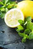 Yellow lemon and green mint on the table Royalty Free Stock Photo