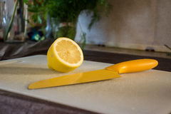 Yellow lemon laying on a white cutting board next to a yellow knife Stock Image