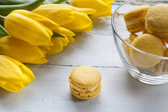 Yellow lemon macaroons and yellow fresh tulips on light wooden background Royalty Free Stock Images