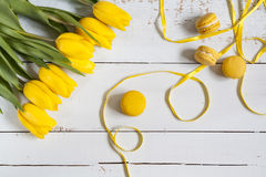 Yellow lemon macaroons and yellow fresh tulips on light wooden background Royalty Free Stock Photos