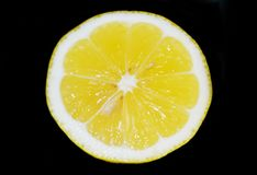 Yellow lemon slice isolated on black background - cutout lemon slice Stock Photo