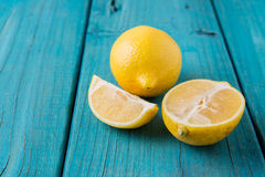 Yellow lemon & slices on vintage blue table Royalty Free Stock Images