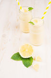 Yellow lemon smoothie in glass bottles with straw, mint leaf, cut lemon, close up. Stock Photography