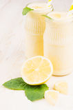 Yellow lemon smoothie in glass bottles with straw, mint leaf, cut lemon, close up. Stock Images