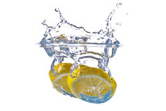 Yellow lemon splashing in clear blue water Royalty Free Stock Photos