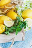 Yellow lemons with mint leaves, wooden background. Yellow lemons with mint leaves on the wooden background Stock Photos