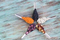 Yellow lentils, black, white, brown, purple kidney beans on spoo. Yellow lentils, black, white, brown, purple kidney beans on metal spoons star composition on Stock Photos