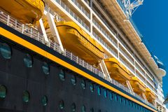 Yellow life boats on a Disney cruise ship. Yellow life boats on a black cruise ship, Disney. Long side view on a bright sunny day on vacation for tourists and royalty free stock image