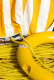 Yellow life buoy, rope and towel Stock Images