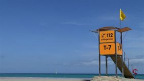 Yellow life guard station with yellow flag at beach. stock footage