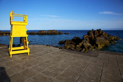 Yellow lifeguard chair cabin  in lanzarote  spain   rock stone s Royalty Free Stock Image
