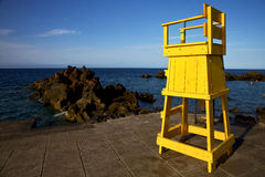 Yellow lifeguard chair cabin  in spain rock stone sky cloud b Royalty Free Stock Photos