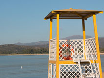 Yellow lifeguard tower on beach. In front of the sea with red life preserver, hills in background royalty free stock images