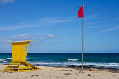 Yellow lifeguard tower. One life guard together red flag on beach. Point of safe, surviving. Coastal view. Royalty Free Stock Photography