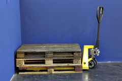 Yellow lift truck. Three wooden Pallets on a yellow lift truck in a industry hall Stock Photos