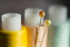 The yellow, light blue, sand color spools of thread and two pins Royalty Free Stock Photos