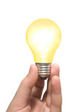 Yellow light bulb in hand royalty free stock photography