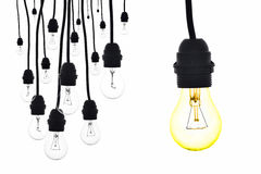 A yellow light bulb hanging next to a number of lamps Royalty Free Stock Image