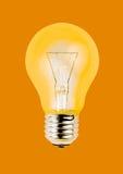 Yellow light bulb isolated on orange background Stock Photo