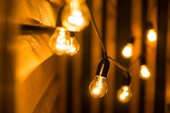 Yellow light bulbs. On wooden background. Christmas lights Stock Images