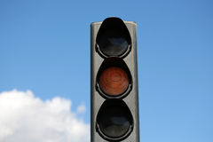 Yellow light-signal of traffic light. Photo closeup traffic light semaphore with yellow light-signal caution indicator signaling device day time against blue sky royalty free stock photography
