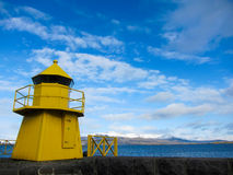 Yellow lighthouse with blue sky and mountains Stock Photos