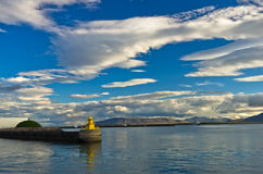 Yellow lighthouse at the entrance to Reykjavik harbor at early morning Royalty Free Stock Photo