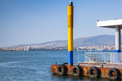 Yellow lighthouse pole on the pier in Izmir city Royalty Free Stock Photos