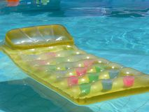 Yellow lilo. Yellow inflatable lilo floating in a blue swimming pool Royalty Free Stock Image