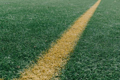 Yellow line on artificial turf grass at sports field Stock Photos