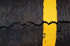 Yellow line on cracked asphalt road Stock Photography