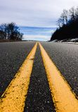 The yellow line down a highway. An up close photo of a yellow line down the middle of the road or highway stock photo