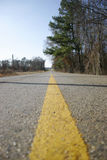 Yellow line on receding road. Low angle view of yellow line on countryside road receding into distance Royalty Free Stock Photography