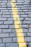 The yellow line on the road receding the stone. The yellow line on the road receding into the distance the stone Stock Image