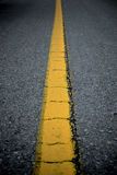 Yellow Line on Street. Cracked yellow line on the straight road Stock Photos