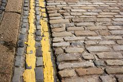 Yellow lines. Modern (no parking) double yellow lines along ancient cobble stones Stock Image