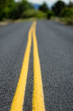 Yellow lines on rural roadway Stock Photography