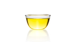 Yellow liquid, oil, in clear glass bowl on white background Royalty Free Stock Photo